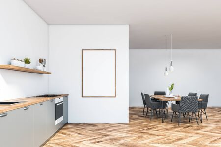 Side view of stylish kitchen with white walls, wooden floor, grey countertops with built in sink and oven, wooden dining table with gray chairs and vertical mock up poster frame. 3d rendering Banco de Imagens