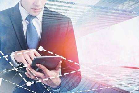 Jeune courtier méconnaissable utilisant une tablette en ville avec une double exposition de graphiques numériques. Concept d'analyse de marché. Image tonique