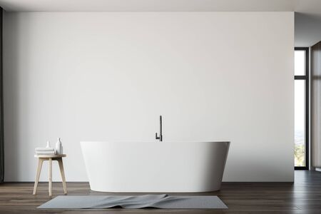 Interior of minimalist style bathroom with white and wooden walls, wooden floor, comfortable white bathtub with carpet near it and narrow window. 3d rendering 스톡 콘텐츠 - 131958439