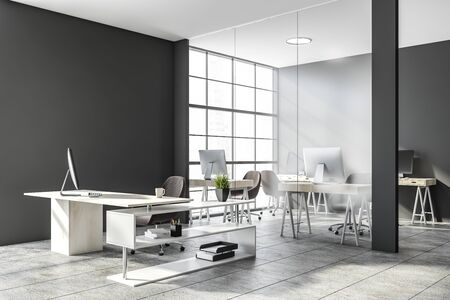 Interior of stylish CEO office with gray and glass walls, concrete floor, comfortable desk and open space area with compact computer tables in background. 3d rendering