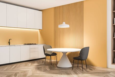 Corner of stylish kitchen with yellow walls, wooden floor, white countertops and cupboards and round dining table with gray chairs. 3d rendering Stock Photo