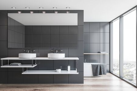 Interior of panoramic bathroom with grey tile walls, wooden floor, double sink with large mirror and comfortable bathtub with shelf above it in background. 3d rendering