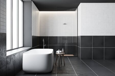 Side view of modern bathroom with white and gray tiled walls, comfortable bathtub standing near window and shower stall with glass wall. 3d rendering Stockfoto