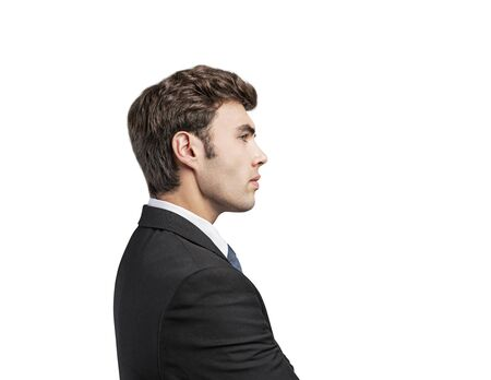 Side portrait of handsome calm serious young businessman in dark suit with brown hair looking forward. Concept of business planning. Isolated on white background