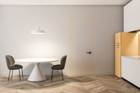 Interior of stylish kitchen with gray walls, wooden floor, white countertops and cupboards, yellow fridge and round dining table with gray chairs. 3d rendering