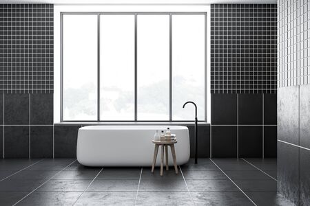 Interior of minimalistic bathroom with black tiled walls and floor, comfortable bathtub standing under window with nice view and chair with towels. 3d rendering