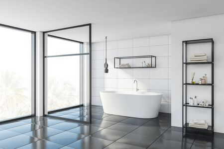 Corner of stylish bathroom with white tile and glass walls, gray floor, comfortable bathtub and shelves with towels and beauty products. 3d rendering