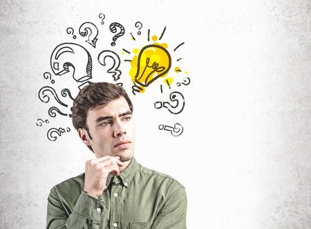 Thoughtful young businessman in dark green shirt standing near concrete wall with question marks and lightbulb drawn on it. Concept of bright idea. Mock up Stok Fotoğraf