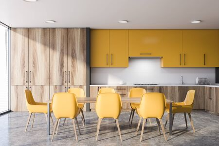 Long wooden dining table with yellow chairs standing in modern kitchen interior with white and gray walls, wooden countertops and yellow cupboards. 3d rendering Stock Photo