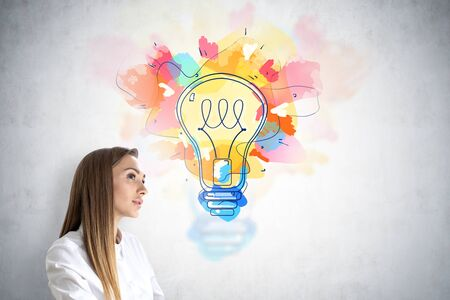 Portrait of thoughtful young businesswoman with long blond hair standing near concrete wall with colorful lightbulb drawn on it. Concept of good idea and brainstorming.