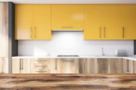 Table for your product in blurry stylish kitchen interior with gray and white walls, wooden countertops with sink and stove and yellow cupboards. 3d rendering