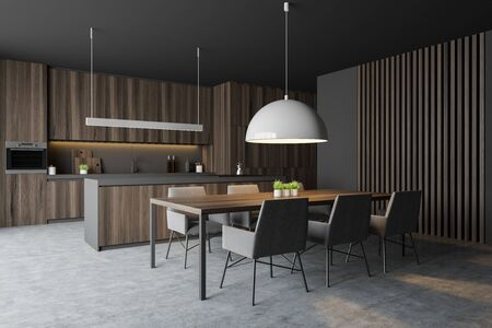 Corner of comfortable kitchen with gray walls, concrete floor, dark wooden countertops and cupboards, cozy island and long dining table with chairs. 3d rendering Stock Photo
