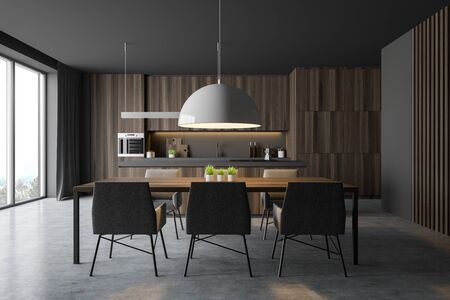 Interior of comfortable kitchen with gray walls, concrete floor, dark wooden countertops and cupboards, cozy island and long dining table with chairs. 3d rendering Stock Photo