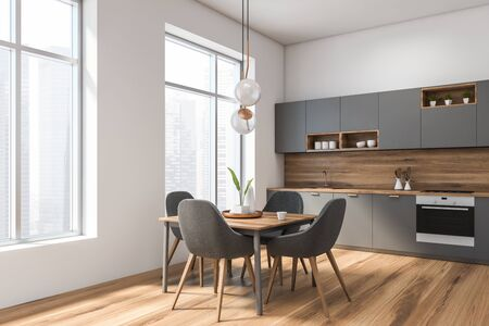 Corner of luxury kitchen with white and wooden walls, wooden floor, grey countertops and cupboards and square wooden dining table with gray chairs. 3d rendering
