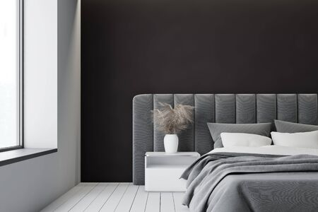 Interior of minimalistic master bedroom with white and black walls, comfortable king size bed with bedside table and soft gray headboard near big window. 3d rendering Фото со стока