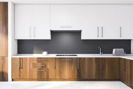 Interior of stylish kitchen with white and gray brick walls, wooden floor, dark wooden countertops with sink and stove and white cupboards. 3d rendering Stock Photo