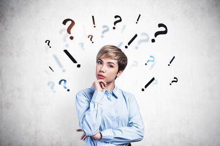 Schöne nachdenkliche junge Geschäftsfrau, die in der Nähe einer Betonmauer mit darauf gezeichneten Frage- und Ausrufezeichen steht. Konzept der Auswahl und Entscheidungsfindung Standard-Bild