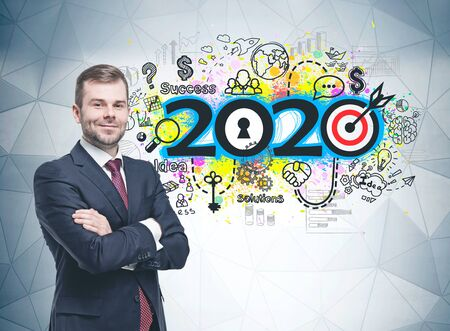 Smiling confident bearded businessman standing with crossed arms near gray wall with colorful 2020 sketch drawn on it. Concept of business planning and new year