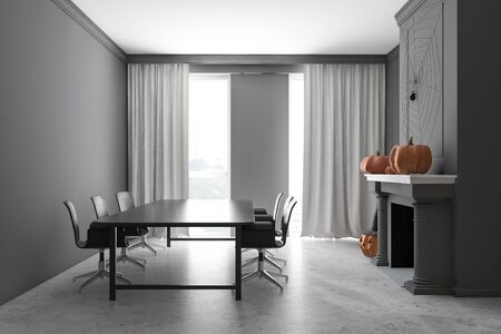 Interior of stylish dining room with gray walls, concrete floor, long black table with chairs and carved pumpkins on fireplace. Concept of Halloween. 3d rendering