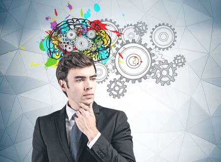 Portrait of pensive young man in suit standing near gray wall with colorful brain sketch with gears drawn on it. Concept of creative and analytical thinking