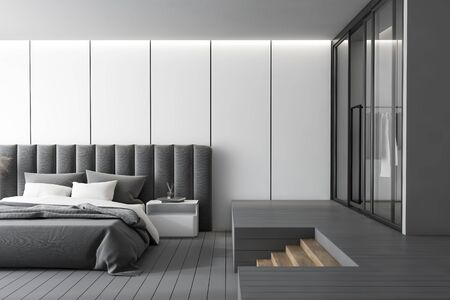 Interior of luxury master bedroom with white panel walls, gray floor, comfortable king size bed with bedside table and wardrobe with stairs leading to it. 3d rendering