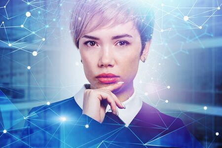 Thoughtful young businesswoman standing over blurry office background with double exposure of network interface. Concept of artificial intelligence. Toned image 版權商用圖片