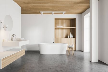 Interior of luxury bathroom with white walls, concrete floor, comfortable bathtub standing near wooden cabinet and stylish sink with round mirror. 3d rendering
