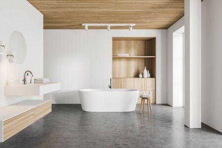 Interno del bagno di lusso con pareti bianche, pavimento in cemento, comoda vasca da bagno in piedi vicino a un mobile in legno e lavandino elegante con specchio rotondo. rendering 3d