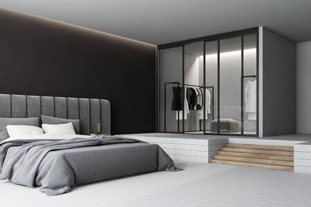 Corner of minimalistic master bedroom with black walls, comfortable king size bed with two bedside tables and soft gray headboard and wardrobe with stairs near it. 3d rendering Banco de Imagens