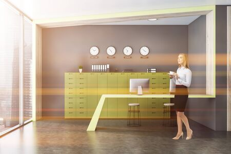 Thoughtful blonde businesswoman standing in modern office with gray walls and floor, narrow computer table, green cabinets and clocks showing world time. Toned image