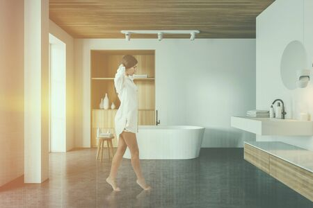 Young woman in nightgown walking in spacious bathroom with white walls, concrete floor, comfortable bathtub, sink with round mirror and wooden cabinet. Toned image double exposure