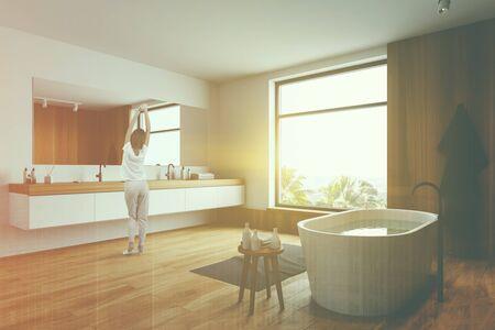 Vista trasera de una mujer en pijama de pie en un cómodo baño con paredes blancas y de madera, bañera con agua y lavabo doble con espejo largo encima. Doble exposición de imagen tonificada
