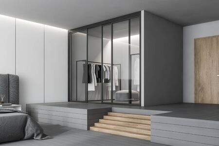 Wardrobe with glass doors standing in luxury master bedroom with white panel and gray walls, gray floor, wooden stairs and comfortable bed. 3d rendering Banco de Imagens