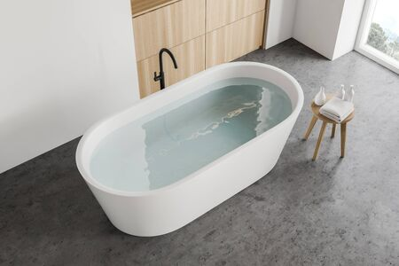 Top view of white bathtub with water standing in modern bathroom with white walls, concrete floor and wooden cabinets. 3d rendering Stock fotó