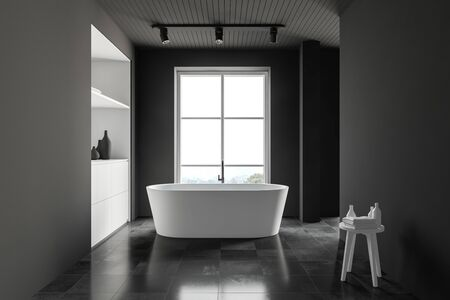 Interior of spacious bathroom with grey walls, tiled floor, cozy white bathtub standing near window and white cabinet. 3d rendering