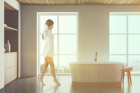 Young woman in nightgown walking in modern bathroom with white walls, concrete floor, comfortable bathtub and wooden cabinet. Toned image double exposure