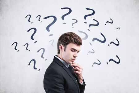Side view of handsome young businessman brainstorming standing near concrete wall with question marks drawn on it. Concept of looking for answers