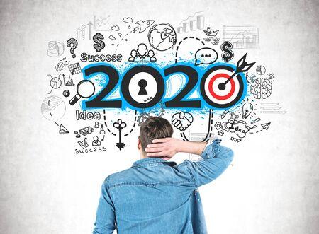 Vista trasera del joven confundido en camisa de jeans mirando el boceto de la estrategia 2020 dibujado en un muro de hormigón. Concepto de planificación y resoluciones de año nuevo.