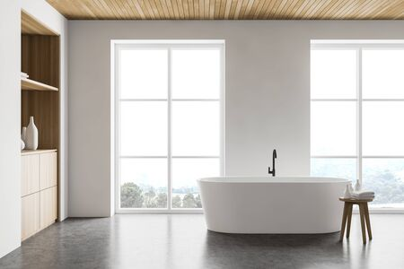 Side view of comfortable bathroom with white walls, concrete floor, cozy white bathtub standing near wooden cabinet and chair with towels. 3d rendering