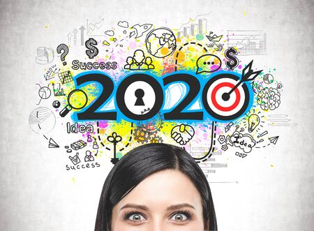 Close up of astonished young woman head near concrete wall with colorful 2020 business strategy sketch. Concept of planning and new year resolutions Foto de archivo