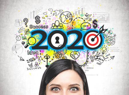 Nahaufnahme eines erstaunten jungen Frauenkopfes in der Nähe der Betonwand mit farbenfroher 2020-Geschäftsstrategieskizze. Konzept der Planung und Neujahrsvorsätze Standard-Bild
