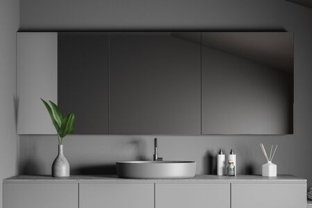 Close up of stylish grey round bathroom sink standing on gray countertop in room with dark gray walls and big mirror. 3d rendering