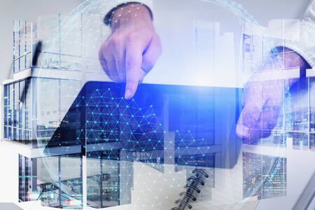 Hands of businessman using tablet in night city with double exposure of office buildings and digital network hologram. Toned image