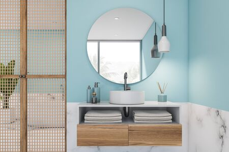 Close up of luxury bathroom with blue and white marble walls, compact sink with round mirror on wooden countertop and bathtub in background. 3d rendering