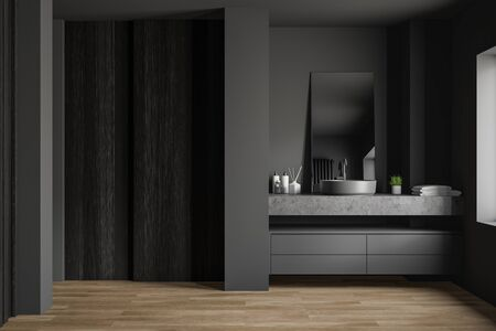 Interior of spacious bathroom with gray and dark wooden walls, wooden floor, comfortable round sink standing on stone countertop and vertical mirror. 3d rendering