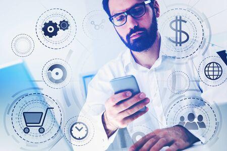 Bärtiger Geschäftsmann mit Brille, der Smartphone in verschwommenem Büro mit Doppelbelichtung der Online-Shopping-Schnittstelle hält. Getöntes Bild