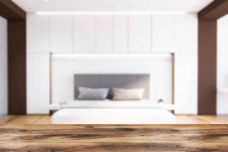 Table for your product in front of blurry interior of modern bedroom with white and brown walls, wooden floor, comfortable king size bed and two bedside tables. 3d rendering