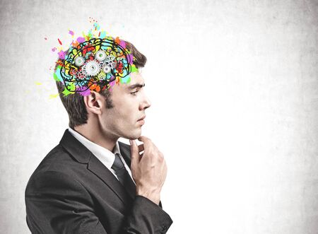 Side view of pensive young businessman standing near concrete wall with colorful brain sketch and gears. Concept of brainstorming. Mock up Stock Photo