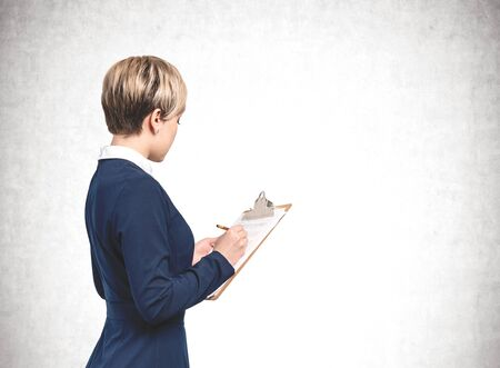 Side view of unrecognizable young businesswoman with short blond hair wearing blue dress and writing in clipboard standing near concrete wall. Concept of planning. Mock up