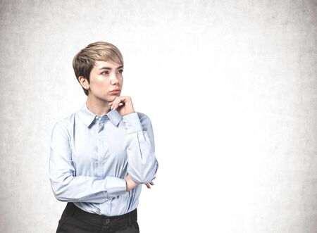 Portrait of serious thoughtful young Asian businesswoman wearing blue shirt and pants standing near concrete wall. Concept of planning. Mock up Stock Photo